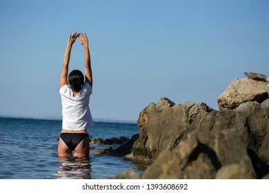 Woman in bikini stretching in the water in beautiful sea landscape, morning sunlight. Exercise and mindfullness