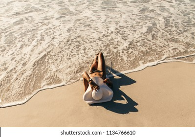 Woman in bikini sunbathing lying near the seashore wearing sun hat with sea waves touching her. Woman on vacation wearing sun hat relaxing at the beach.