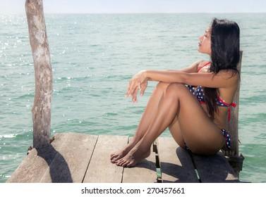 woman in bikini sunbathing on mole over the sea
