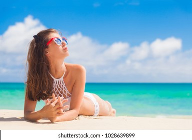 woman in bikini and sunglassesrelaxing on tropical beach/