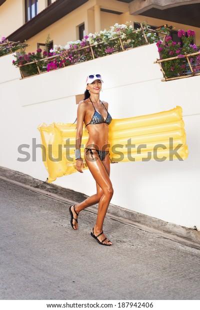 Woman in bikini in suntan oil with yellow float walking on the summer street Outdoors
