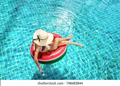 Woman bikini swimming pool on watermelon rubber ring relaxing vacation enjoying on summer season, Top view.