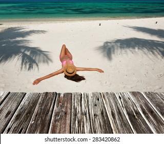 Woman in bikini at tropical beach under the palm tree shadow