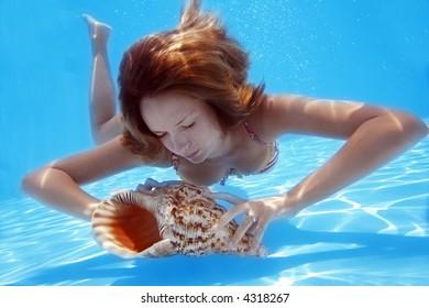 Woman in bikini underwater in pool with conch