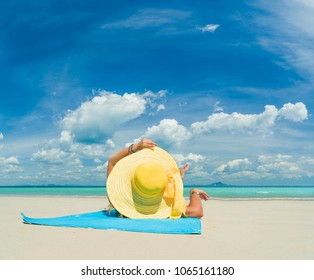 Woman in bikini wearing a yellow hat suntanning at tropical beach