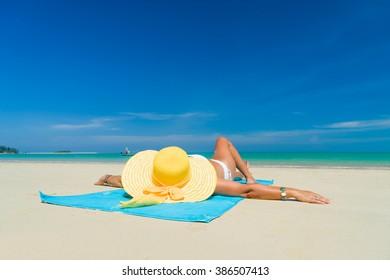 Woman in bikini wearing a yellow hat suntanning at tropical beach