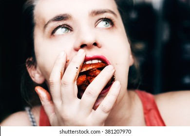 Woman binge eating french fries, mouth full of food