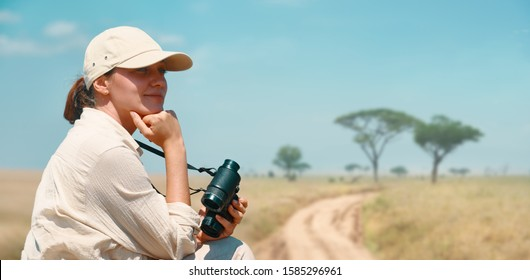 Woman with binoculars enjoying a beautiful view of the African savannah during a safari tour in Tanzania and Kenya.