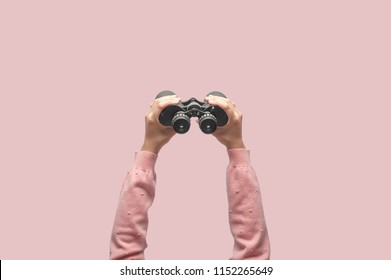 Woman with binoculars on retro pink background, looking through binoculars, journey, find and search concept.