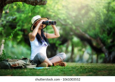 Woman with Binoculars and Telescope in green Forest.Travel concept.