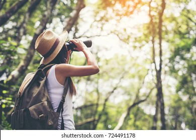 Woman with Binoculars and Telescope in Rain Forest.Travel concept.