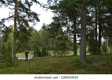 Woman birdwatching in forest