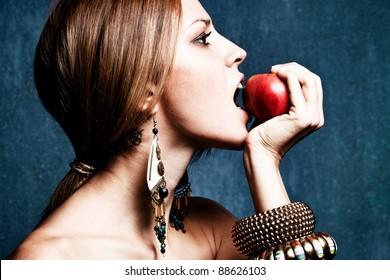 woman bite an apple, profile, studio shot