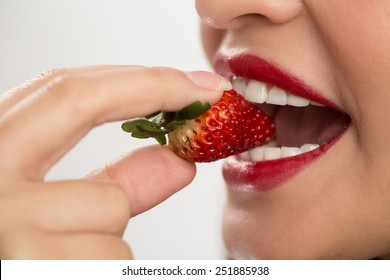 Woman biting a strawberry