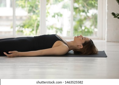 Woman in black activewear practises yoga lying resting do Dead Body Savasana Corpse pose relax gain strength in cozy light room, view from window greenery sunlight idyllic place for effective work out