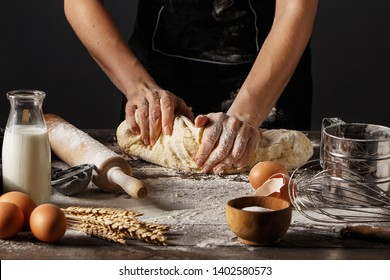 Woman in black apron kneading dough on wooden table with spelt flour, raw eggs, bottle with milk, rolling pin and wheat spikes. Step by step recipe of cooking dough, bakery products or pastry