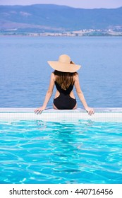 Woman in a black bathing suit and a hat sitting on the edge of the pool
