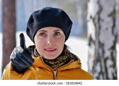 woman in a black beret shows thumb