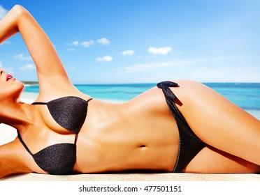 Woman with black bikini on the beach.Beautiful tanned skin.