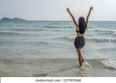 Woman in black bikini and sarong standing on beach.