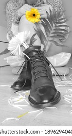 a woman in black boots, black and white, with yellow blossom
