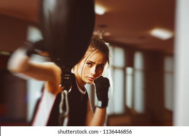 Woman with black boxing wraps on hands boxing in ring. Active girl fight. Right hook with motion blur