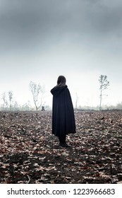 Woman in black cape in moody countryside.