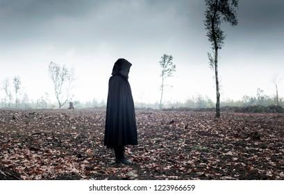 Woman in black cape in moody landscape.