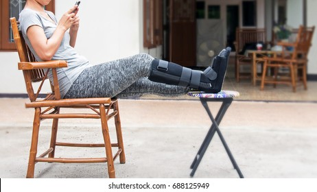 woman with black cast on leg sitting on wood chair, body injury concept.