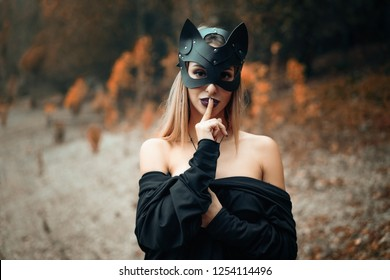 a woman in a black cat mask stands on the background of nature.