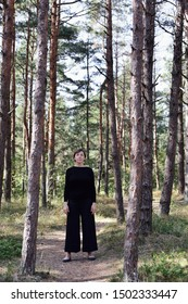 Woman in black clothes is standing in the forest