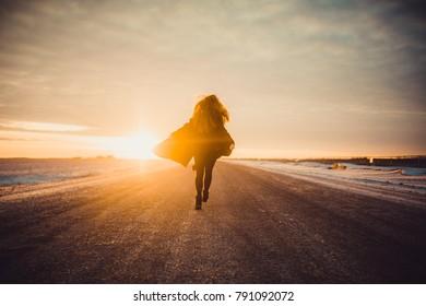 woman in black coan in sunset on road