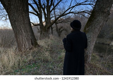 Woman in black coat and hat in autumn park among trees