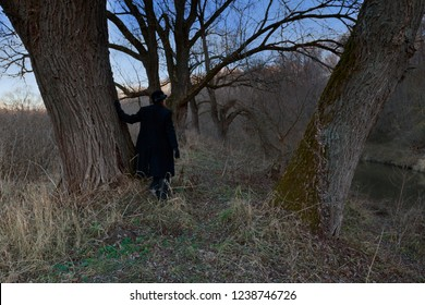 A woman in a black coat stands among the trees in nature