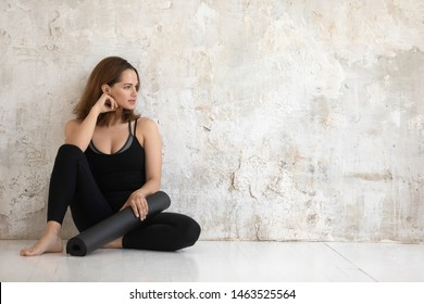Woman in black comfortable sports cloth holds rolled yoga mat look away resting leaned against beige grunge wall copy space for sportswear fashion store ad, finished workout girl gather energy concept
