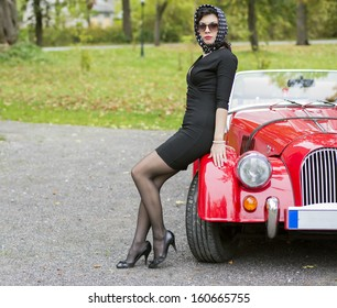 Woman in black with dark glasses with car