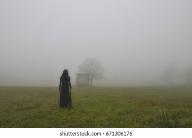 Woman with black dress, alone in the fog, Italy