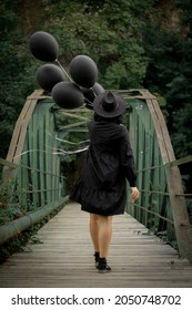 A woman in a black dress and a hat with black balloons walks along a green bridge