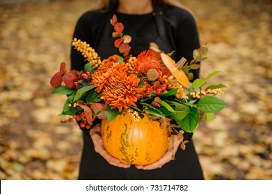 Woman in a black dress holding a beautiful pumpkin with lovely autumn flowers on the background of yellow leafs