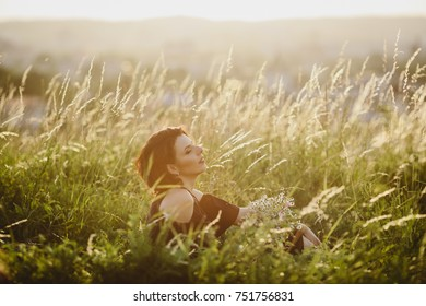 Woman in black dress lies on the summer field in the rays of sun