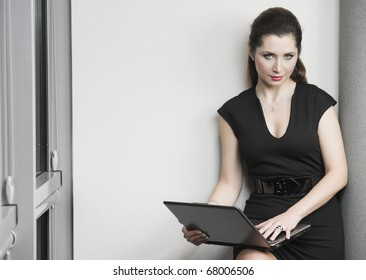 Woman with the black dress in the office with a laptop