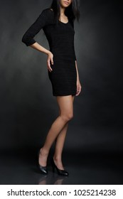 Woman in black dress on the dark background