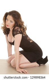 A woman in a black dress on her knees looking seductive.