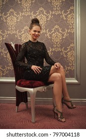 Woman in black dress sitting on chair
