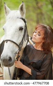 Woman in black dress stands with white horse in park.