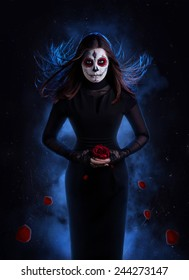 Woman in black dress with sugar skull makeup holding red rose with falling petals at dark background