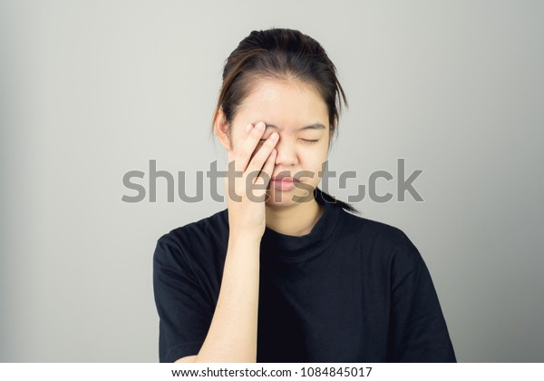Woman in a black dress is touching head to show her headache. Causes may be caused by stress or migraine. Or because too much work. The concept of stress from hard work is bad for health.