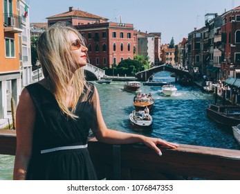 Woman in black dress walking in the sunny street in Venice, Italy Toned Image