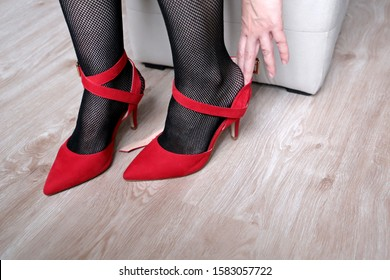 Woman in black fishnet stockings trying on red shoes on high heels. Concept of shoe size, female fashion, tired legs or foot pain