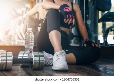 woman in black fitness suite sitting and breaking relax while exercise workout in gym